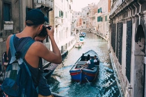 man_taking_a_photo_of_venice_canal