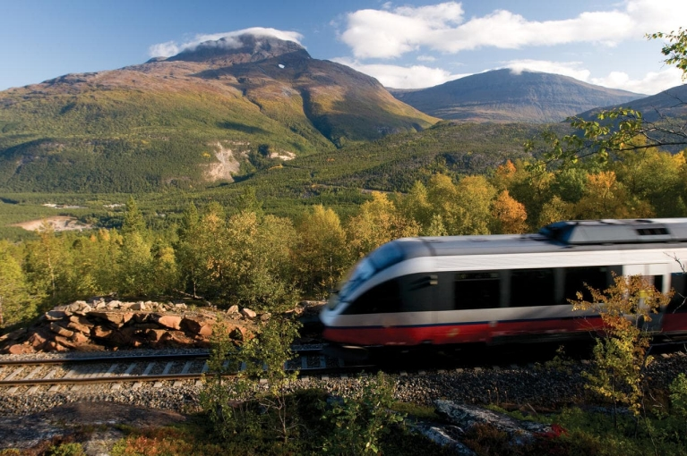 Photo d'un train norvégien filant à vive allure à travers un paysage vallonné | Trains en Norvège