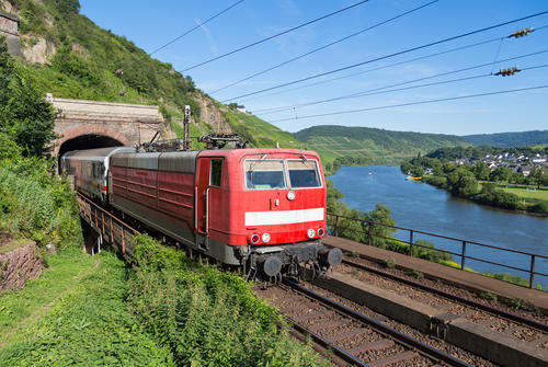 Train leaving a tunnel near the river Moselle in Germany