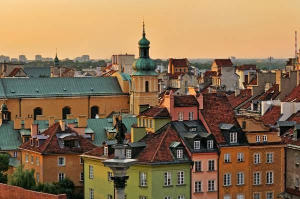 Image of traditional rooftops of buildings in the Warsaw skyline with a hazy yellow sky
