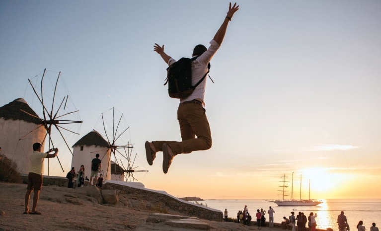 Image of a man jumping in the air above Greek island Mykonos. In the background the sun sets over windmills and the sea